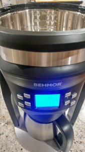 A view of the Behmor Brazen Plus coffeemaker from the top down. The stainless steel reservoir is shiny and new, and the display is brightly lit.