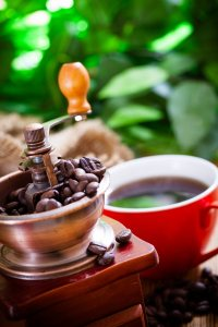 An antique hand-operated coffee grinder is overflowing with beans. It's sitting next to a cup of rich, fresh-brewed coffee. Morning sunlight reflects off some out-of-focus objects in the background.