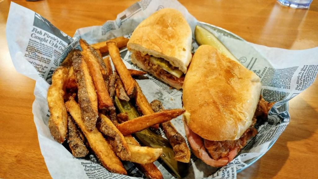 A plate containing a Cuban sandwich, french fries, and a pickle slice. The meal sits on top of a paper lining, which is meant to resemble a page from an old newspaper.