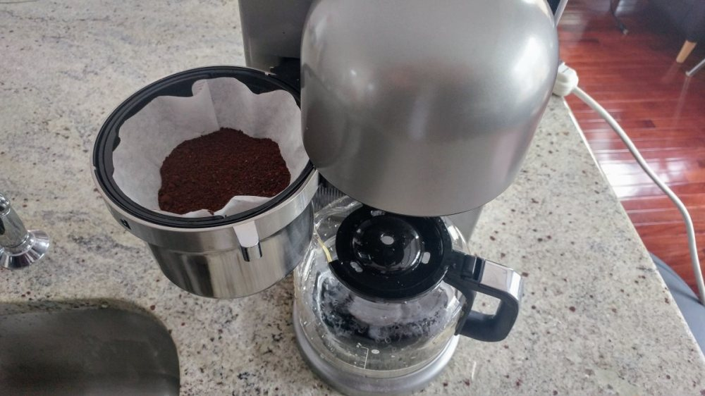 A top-down view of the KitchenAid KCM0802 coffeemaker. The brew basket is open, revealing that it is lined with a paper filter and about half full of ground coffee.