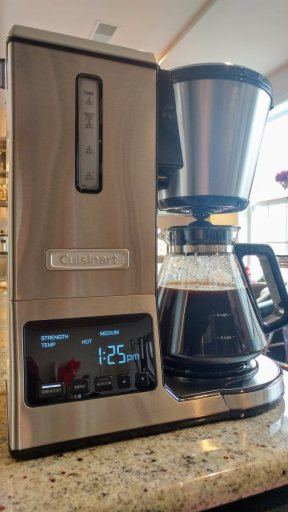 A Cuisinart CPO-800 coffeemaker sits on a granite countertop. The display shows the strength and temperature settings, as well as the time. The carafe is about 75% full of rich, dark coffee. Daylight streams in through a window in the background.