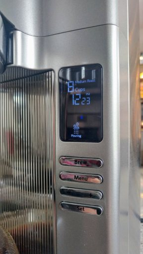 "A closeup of the display panel of the KCM0802. The display currently indicates that it's brewing 8 cups on medium roast, and is currently in the ""pouring"" cycle."