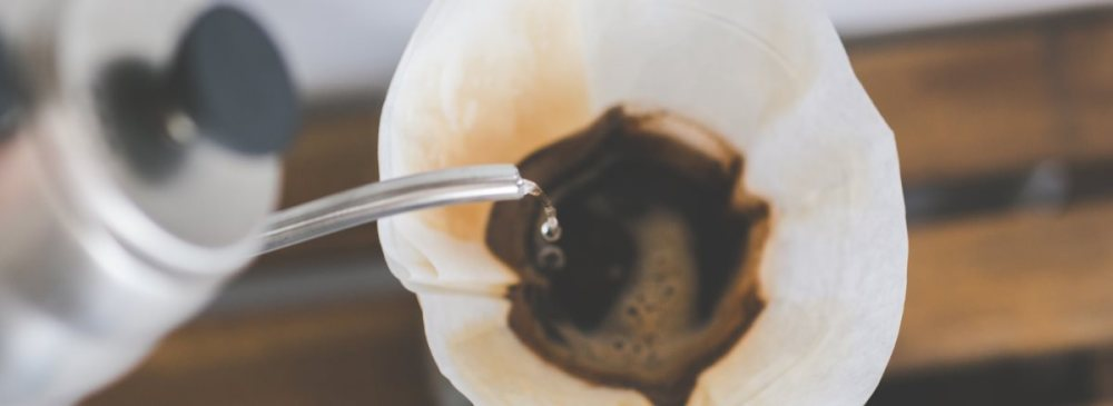 A closeup of a cup of coffee being made using the pourover or Chemex method. A stainless steel gooseneck kettle slowly pours water into a filter.