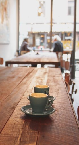 Two coffee cups sit unattended on a long wooden table. Two unidentifiable people talk together at an adjacent wooden table. A large floor-to-ceiling window looks out over a streetscape outside, suggesting this may be downtown in some unknown city.