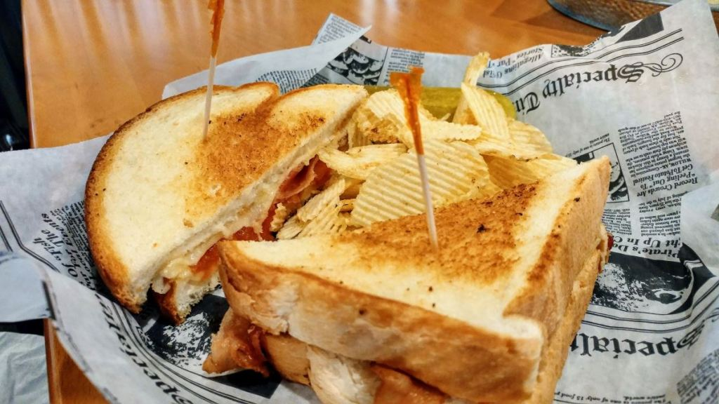 A plate containing a grilled cheese sandwich sliced in half, potato chips, and a pickle sliced lengthwise. The food sits on top of a paper liner, which is meant to resemble a page from an old newspaper.
