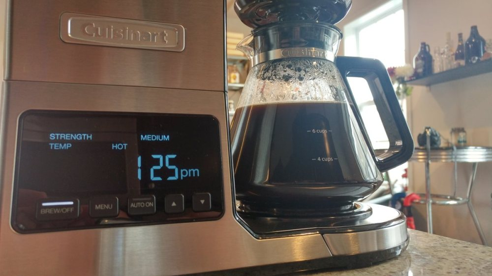 "A closeup shot of the coffeemaker, focusing on the display. Five buttons are visible, labeled ""brew / off"", ""menu"", ""auto on"", ""up arrow"", and ""down arrow"". The carafe is mostly full of rich, dark coffee. A chrome pub table is visible in the background, as are several growlers resting on a shelf."