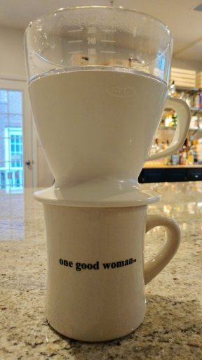 "The OXO Good Grips Pourover coffeemaker is placed on top of a coffee mug from a local store (""One Good Woman""). The coffemaker resembles a small coffee mug. On top of the coffeemaker is the plastic water reservoir, which holds up to 12 cups of hot water."