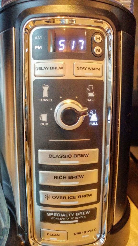 "The control panel for the Ninja Coffee Brewer. A display shows the current time. A rotary knob selects the size of the brew. Buttons from top to bottom are ""Delay Brew"", ""Stay Warm"", ""Classic Brew"", ""Rich Brew"", ""Over Ice Brew"", ""Specialty Brew (Concentrated Coffee)"", and ""Clean""."