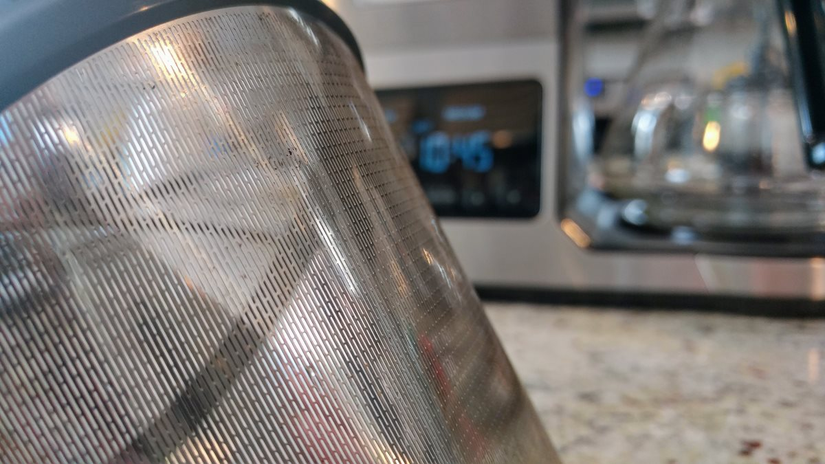 A closeup of the permanent filter. Unlike most permanent filters, which resemble metal screens, this filter has a series of small vertical slots several millimeters long. The CPO-800 coffeemaker is visible in the background.