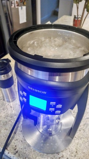 The Behmor Brazen Plus running its calibration program. The lid is off, exposing a reservoir full of boiling water.