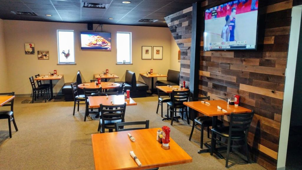 York Street Grille's dining room. Six standalone tables and three booths seat 2 to 4 patrons each. A TV is mounted on the wall showing a baseketball game. One wall is covered in wooden planks. A rooster statue is visible in one of the two vertical windows.