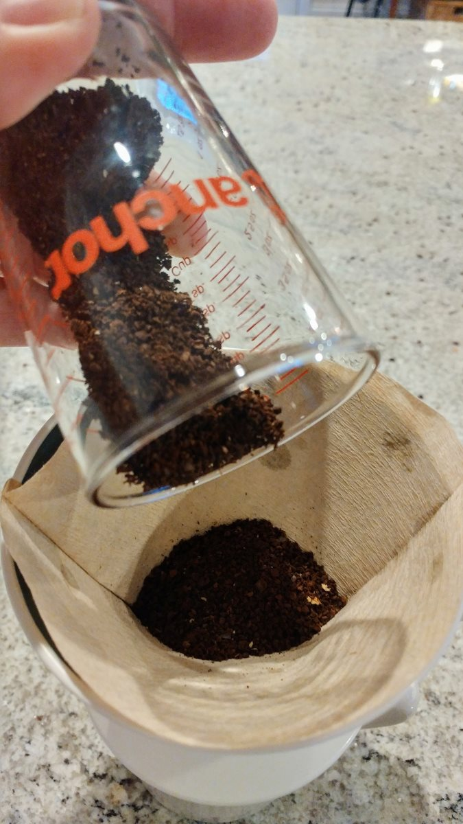 Ground coffee is poured from a glass measuring cup into the OXO Pourover. One of the included paper filters is used to hold the coffee grounds.