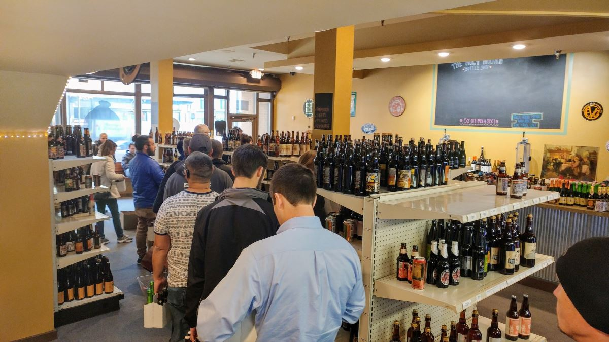 A line of customers winds around the display shelves in a craft beer store. A window overlooks Market Street in York, while a chalkboard that used to list their specials now sits sadly empty. Roughly a dozen customers are visible, mostly men in their 20s and 30s. Several dozen varieties of craft beers are visible.