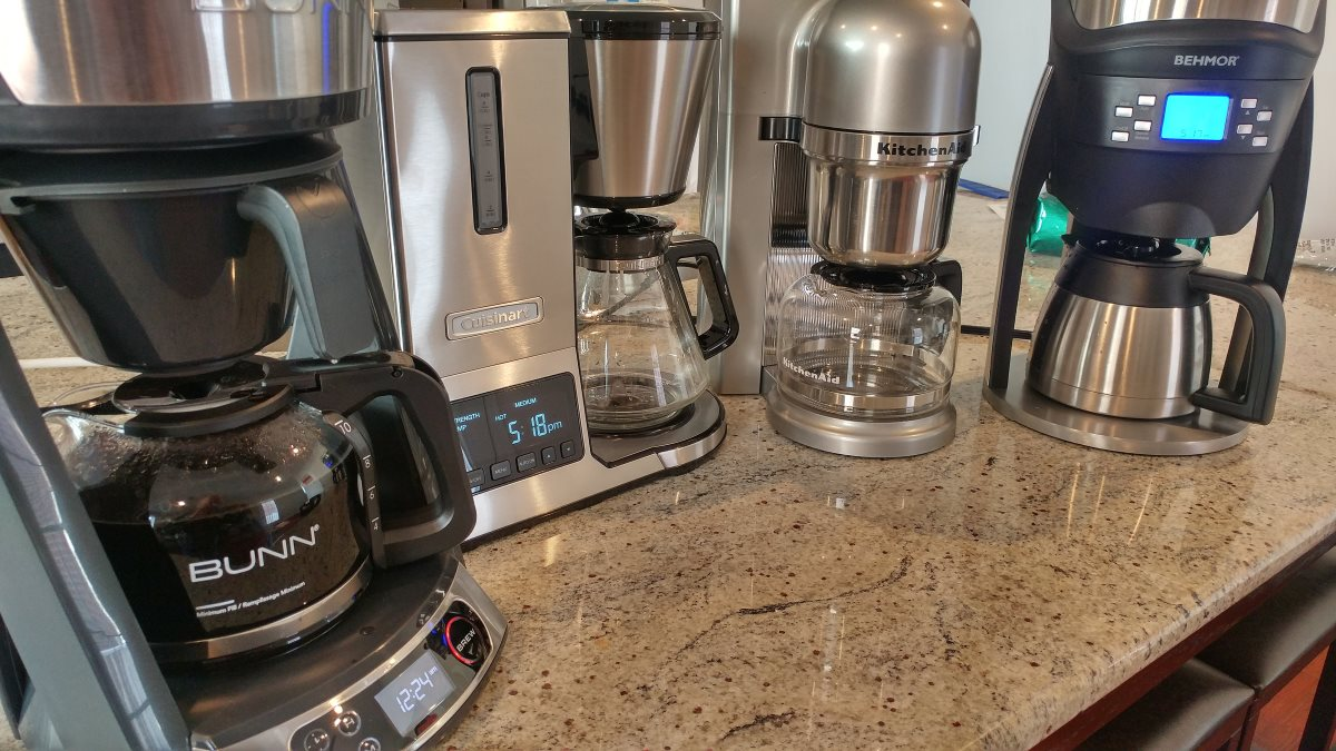 Four of the tested coffee makers are pictured on a granite countertop. They are the Bunn HB, the Cuisinart CPO-800, the Kitchenaid KCM0802, and the Behmor Brazen Plus. The Bunn's carafe is full of rich, dark coffee.